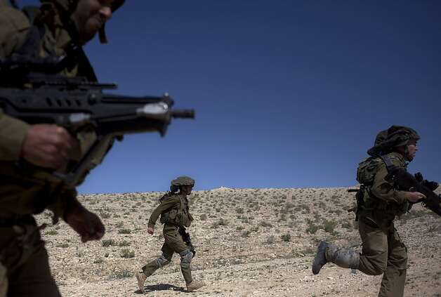 Israeli soldiers run as they participate in a drill near Revivim southern Israel, Thursday, March 7, 2013. On a dusty field in Israel's southern desert, the military is gearing up for the next battle against a familiar foe: Hezbollah guerrillas in Lebanon. As the Syrian civil war intensifies on Israel's northern doorstep, military planners are growing increasingly jittery that the fighting could spill over into Israel, potentially dragging Hezbollah into the fray. (AP Photo/Sebastian Scheiner) Photo: Sebastian Scheiner, Associated Press