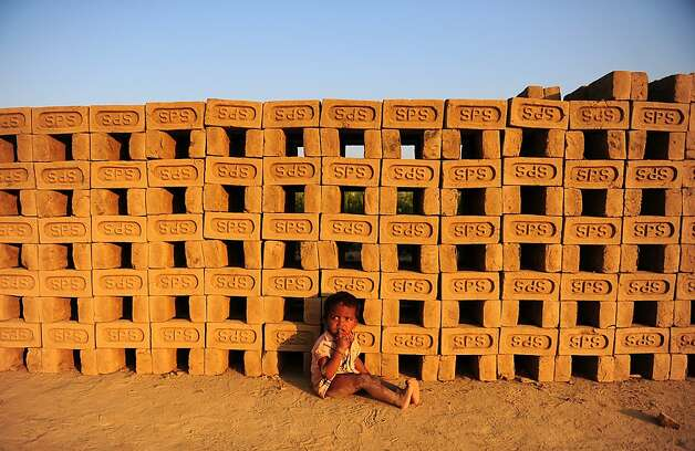 TOPSHOTS  The child of an Indian female labourer sits on the ground at a  brick factory in Allahabad on March 7, 2013, on the eve of International Women's Day. Women have always faced higher unemployment rates than men, and the sluggish global economy in recent years has only made the situation worse, the International Labour Organisation said in December 2012. AFP PHOTO/ Sanjay KANOJIASanjay Kanojia/AFP/Getty Images Photo: Sanjay Kanojia, AFP/Getty Images