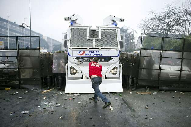 TOPSHOTS  A protesting Goodyear France worker faces riot police in front of the French headquarters of the US tyre and rubber firm in the western Paris suburb of Rueil-Malmaison on March 7, 2013 during a board meeting. Goodyear announced in January 2013 that it would close a factory in Amiens, northern France, that employs 1,250 people by the end of 2014. With little demand for its products, Goodyear has suffered losses of about 50 million euros ($67 million) a year at the plant.  AFP PHOTO / LIONEL BONAVENTURELIONEL BONAVENTURE/AFP/Getty Images Photo: Lionel Bonaventure, AFP/Getty Images