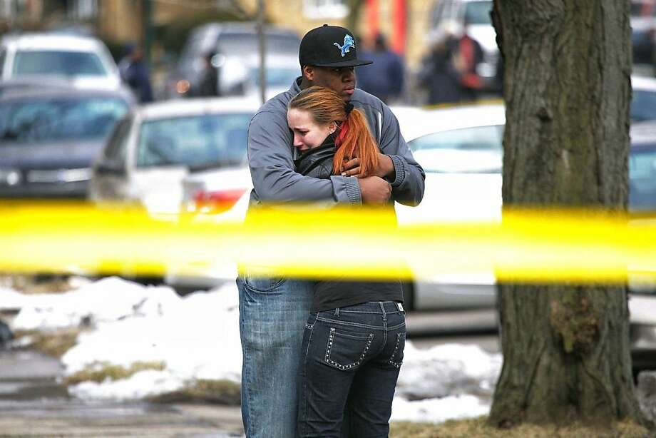Family members comfort each other at the scene where three bodies were found in a house on the 11300 block of  Coyle Street in Detroit on Thursday March 7, 2013. Police say the bodies of three people who had been shot were found in a vacant house on Detroit's northwest side. (AP Photo/Detroit Free Press, Ryan Garza)  DETROIT NEWS OUT;  NO SALES; MAGS OUT; TV OUT; MANDATORY CREDIT Photo: Ryan Garza, Associated Press