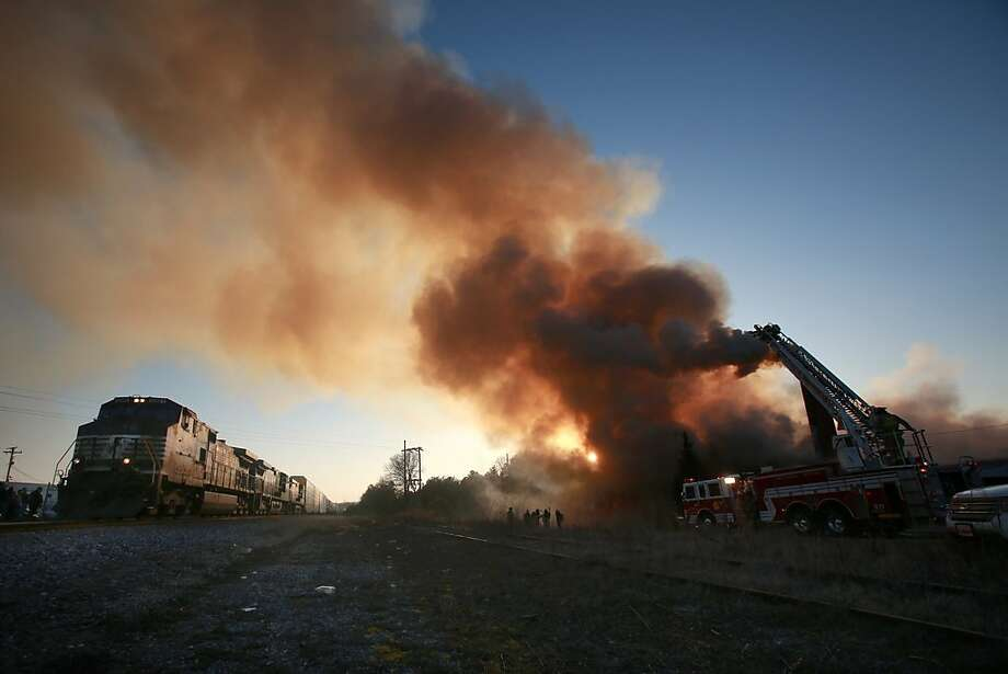 A northbound Norfolk Southern train glides by the scene of a fire at the Minette Mills building on Main Street in Grover, N. C. on Thursday, March 7, 2013. (AP Photo/The Star, Ben Earp) Photo: Ben Earp, Associated Press