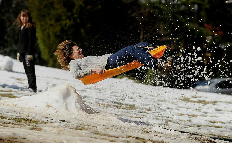 Vera Hoffman, 49, takes to the air as she heads down a partially snow covered  Trench Hill  in Fredericksburg, Va. on Thursday, March 7, 2013. As much as 6 inches of wet snow was measured in parts of Fredericksburg as a result of Winter Storm Saturn. (AP Photo/The Free Lance-Star, Peter Cihelka) Photo: Peter Cihelka, Associated Press