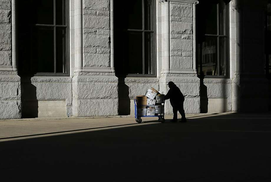 A U.S. Postal Service employee pushes a cart full of mail through a patch of sunlight outside of an office building in Baltimore, Thursday, March 7, 2013. Dry and sunny weather greeted the Mid-Atlantic region a day after it was threatened by a snowstorm. (AP Photo/Patrick Semansky) Photo: Patrick Semansky, Associated Press