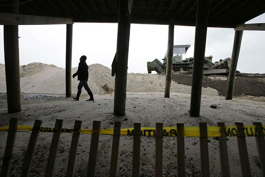 As heavy machinery is pushing sand to hastily rebuild a breached dune, Scott Clayton, of Bay Head, stops by his family's ocean front home damaged by Superstorm Sandy in Mantoloking, N.J., to check on new storm damage Thursday, March 7, 2013, after a storm overnight Thursday, with pounding surf broke through a temporary dune during the early-morning high tide. Flooding also remained a problem in other shore towns.Water on roadways was also forcing closures in towns including Monmouth Beach, Absecon, Aberdeen, Egg Harbor Township and Wildwood. (AP Photo/Mel Evans) Photo: Mel Evans, Associated Press