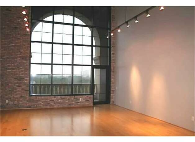 Gigantic arched window with views of downtown Houston.