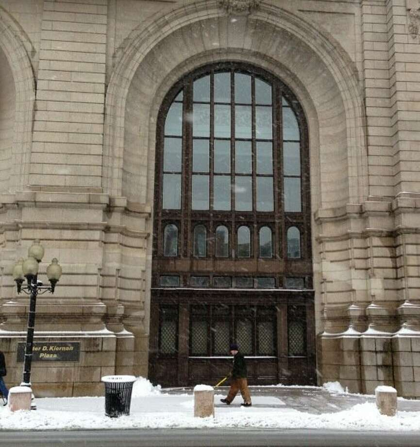 A worker clears snow from the walk in front of Kiernan Plaza in Albany. (Skip Dickstein / Times Union)