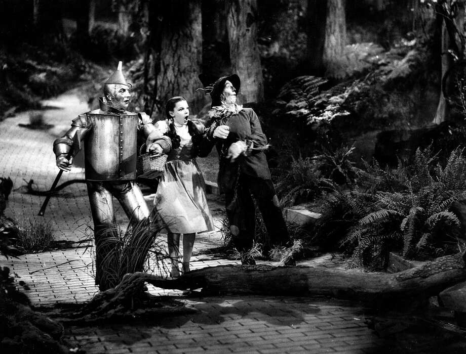 "Judy Garland who played the role of Dorothy, flanked by, left, Jack Haley who was the Tin man, and Ray Bolger who played the Scarecrow, walking on the yellow brick road in ""The Wizard of Oz."" Photo: Paul Popper/Popperfoto, Getty Images / Popperfoto"