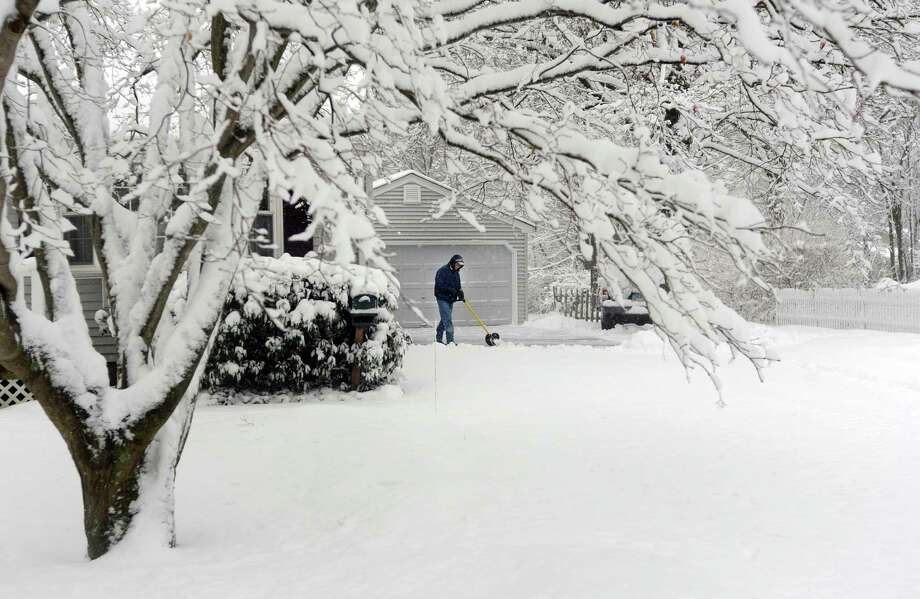 Bill Smith shovels his driveway on Szost Dr. in Fairfield, Conn. as snow continues to fall on Friday, March 8, 2013. Photo: Cathy Zuraw / Connecticut Post