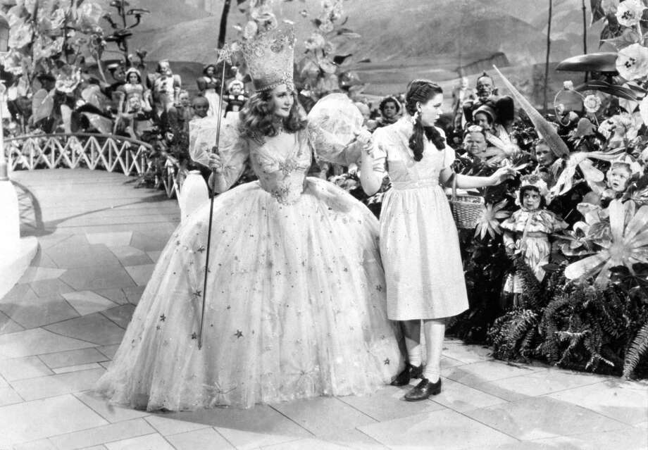 Judy Garland (right) and Billie Burke link hands, surrounded by Munchkins. Photo: Getty Images / Moviepix