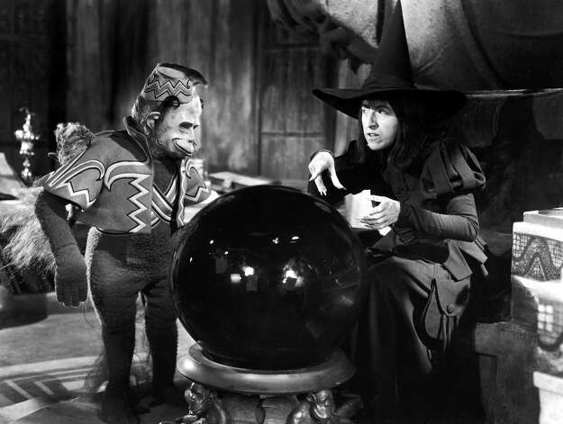 Margaret Hamilton as the Wicked Witch, and a winged monkey look into a crystal ball. Photo: Getty Images / Moviepix