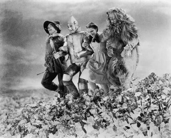 Ray Bolger, Jack Haley, Judy Garland, and Bert Lahr run arm in arm through a field of poppies. Photo: Getty Images / Moviepix