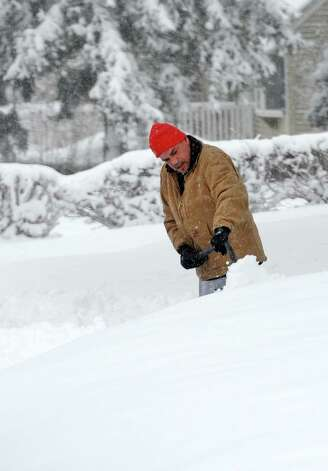 Charlie Perez shovels his driveway on Szost Dr. in Fairfield, Conn. as snow continues to fall on Friday, March 8, 2013. Photo: Cathy Zuraw / Connecticut Post