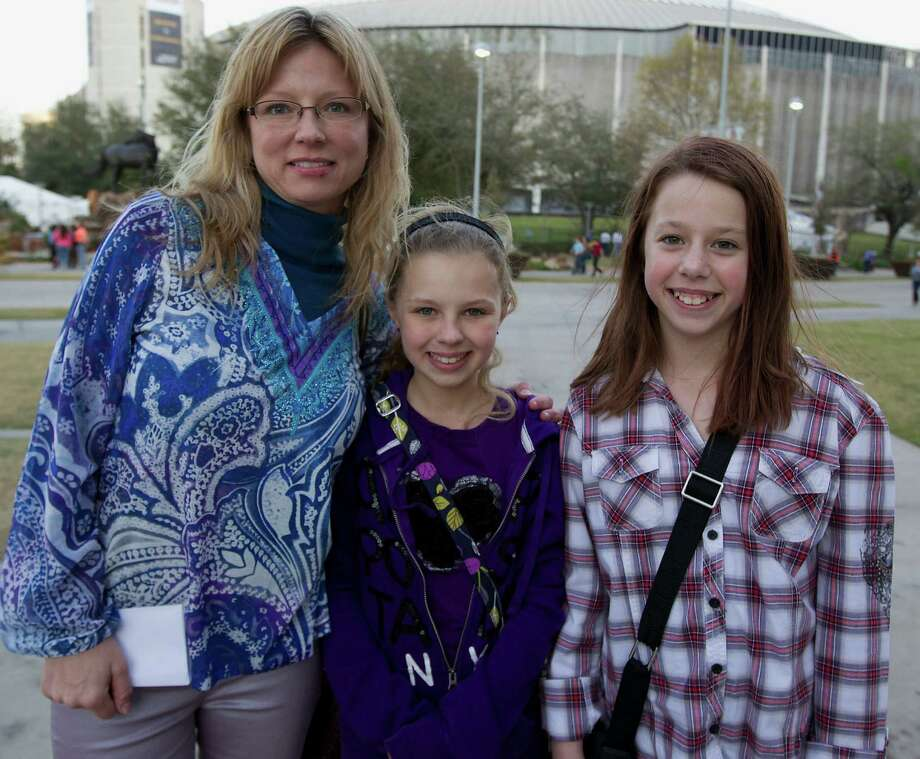Shelly Lang left, and her eleven-year-old daughter Alexis Lang center, and Davin Watt right, arrive at Reliant Park for the RodeoHouston performance featuring Bruno Mars Thursday, March 7, 2013, in Houston. Photo: James Nielsen, Houston Chronicle / © 2013  Houston Chronicle