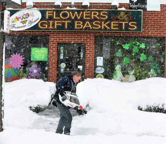 A worker spreads salt in front of Forever Yours Flowers and Gift Baskets as Danbury area residents dig out during Friday morning's snow, in Conn. March 8, 2013. Photo: Michael Duffy / The News-Times
