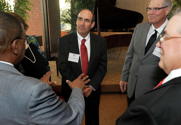 Lamar presidential candidate Carl Stockton, center, talks with with Robert Turner during a candidate reception at the school's library Thursday night. Dean College of Business University of Oklahoma  Guiseppe Barranco/The Enterprise Photo: Guiseppe Barranco, STAFF PHOTOGRAPHER / The Beaumont Enterprise