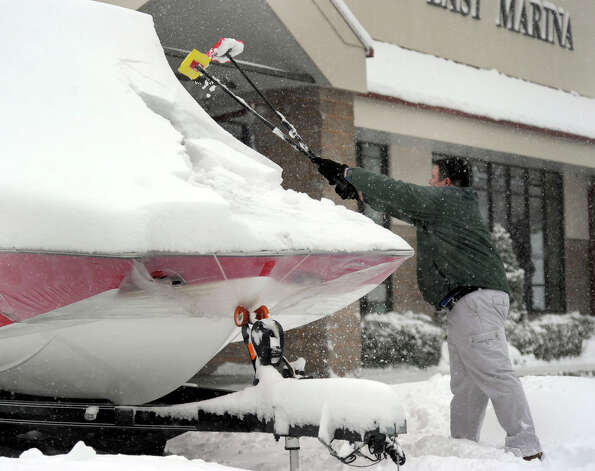 Ryan Slater clears snow from the boats at Candlewood East Marina in Brookfield, Conn. Friday, March 8, 2013. Photo: Carol Kaliff / The News-Times