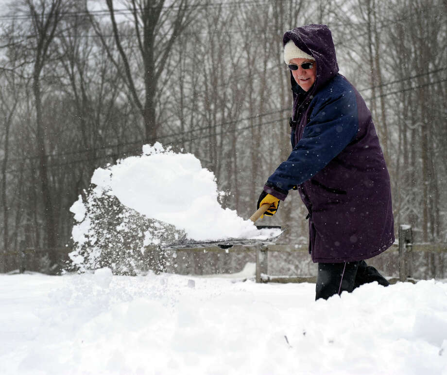 While her husband, Frank, uses the snowblower on the driveway, Gerry Ferris shovels the walks of their home in Brookfield after an over night snowfall, Friday, March 8, 2013. Photo: Carol Kaliff / The News-Times