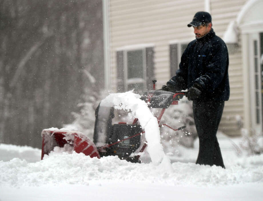 Muthu Muthuswamy of Brookfield uses a snowblower to clear his driveway after an overnight snow fall, Friday, March 8, 2013. Photo: Carol Kaliff / The News-Times