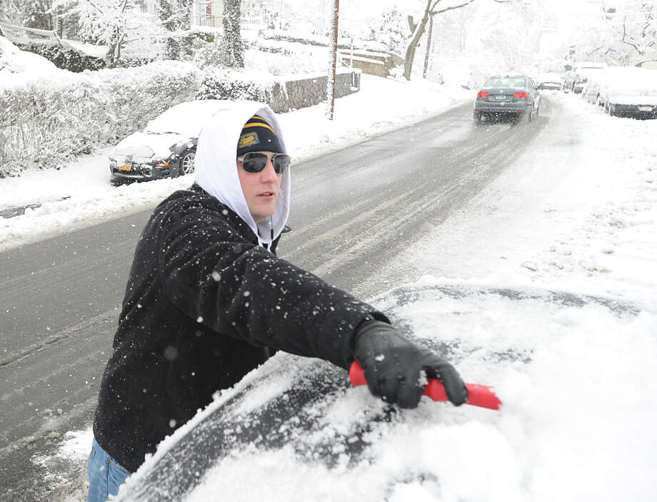 Tim Ludlum clears snow from his car on Richland Road during the snow storm that hit Greenwich, Friday morning, March 8, 2013. Ludlum said the snow and digging out from it, caused him to go into work late. Photo: Bob Luckey / Greenwich Time