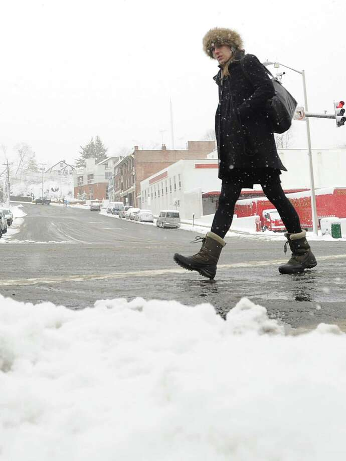 A woman walks on Greenwich Avenue during the snow storm that hit Greenwich, Friday morning, March 8, 2013. Photo: Bob Luckey / Greenwich Time
