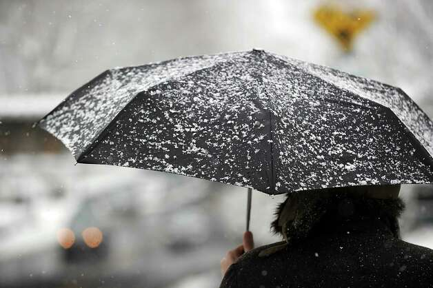 A snow-covered umbrella is held by a man on Greenwich Avenue during the snow storm that hit Greenwich, Friday morning, March 8, 2013. Photo: Bob Luckey / Greenwich Time