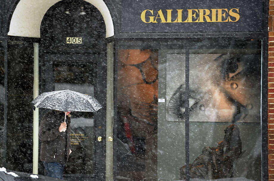 A man with an umbrella walks past an art gallery on lower Greenwich Avenue during the snow storm that hit Greenwich, Friday morning, March 8, 2013. Photo: Bob Luckey / Greenwich Time