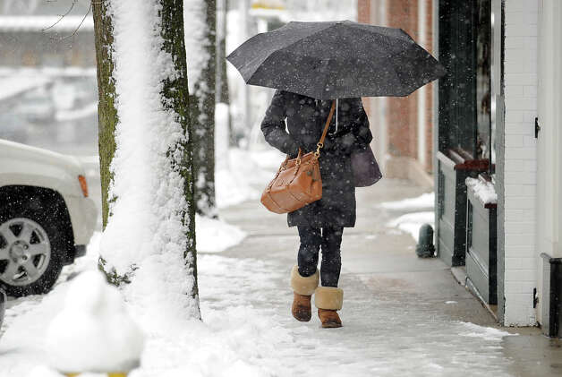 A woman with an umbrella heads north on Greenwich Avenue during the snow storm that hit Greenwich, Friday morning, March 8, 2013. Photo: Bob Luckey / Greenwich Time