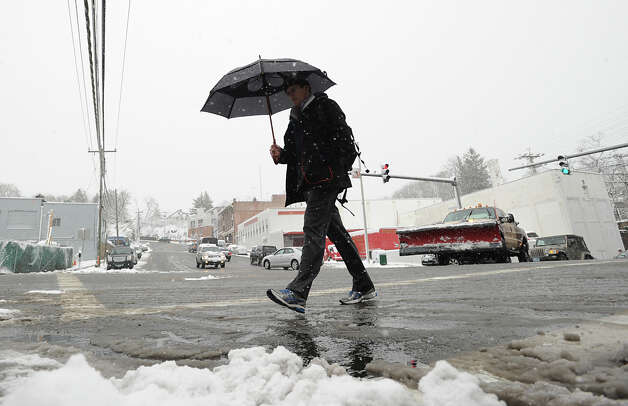 A man carrying an umbrella crosses Greenwich Avenue during the snow storm that hit Greenwich, Friday morning, March 8, 2013. Photo: Bob Luckey / Greenwich Time