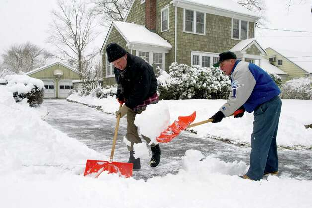 Mark Bianco, left, and his father, Ted, right, shovel snow in Stamford on Friday, March 8, 2013. Photo: Lindsay Perry / Stamford Advocate