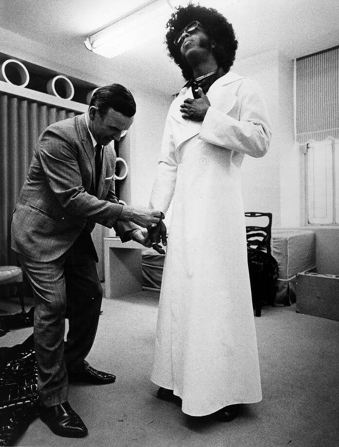 Sly Stone gets some help with his wardrobe. Photo: Michael Ochs Archives, Getty Images / Michael Ochs Archives