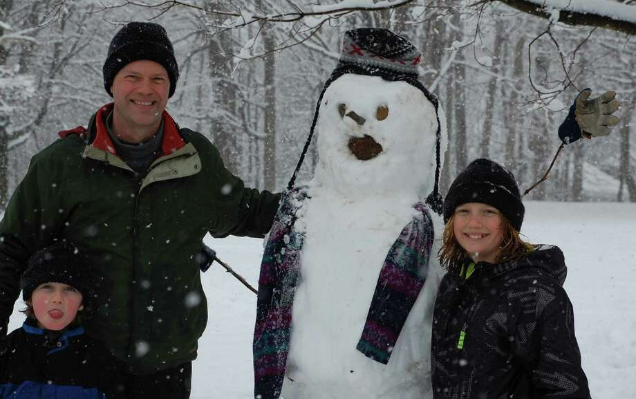 Craig Patton,the  husband of Saugatuck Congregational Church's Rev. Alison Patton, joined his children Ian, 7, left, and Tobey, 10, fashioned a friendly snowman in the freshly fallen snow Friday morning. WESTPORT NEWS, CT 3/8/13 Photo: Jarret Liotta / Westport News contributed