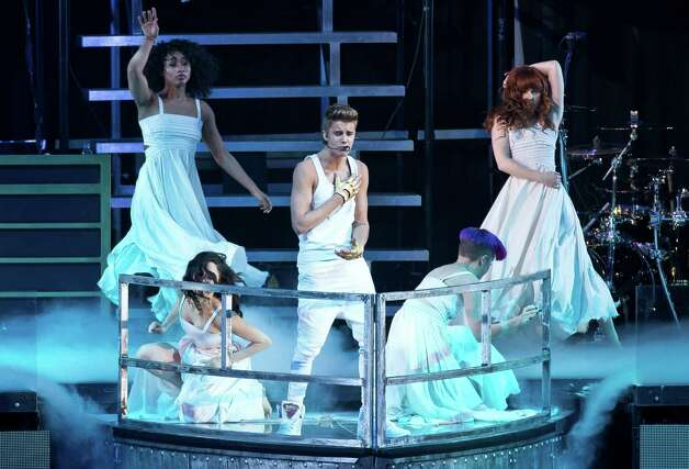 FILE - In this Monday, March 4, 2013 file photo, Canadian singer Justin Bieber performs at the O2 Arena in east London.  Bieber is recovering after fainting backstage at a concert in London. A spokeswoman for Bieber said Thursday, March 7, 2013, that the 19-year-old pop star was given oxygen and took a 20-minute reprieve after fainting backstage at London's O2 Arena. (Photo by Joel Ryan/Invision/AP, File) Photo: Joel Ryan, Associated Press / Invision