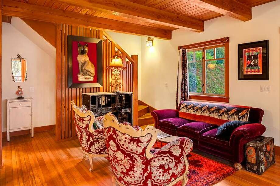 Living room of 14036 38th Ave. N.E. The 1,590-square-foot home, built in 1999, has one bedroom, one bathroom, exposed wood beams and ceilings, a finished daylight basement, a front porch, a wrap-around deck, a balcony, a patio and views of Lake Washington and the Cascades on a 10,225-square-foot lot. It's being sold with three other vacant view lots and is listed for $1.08 million. Photo: Courtesy Kelly And Kian Pornour/ Windermere Real Estate