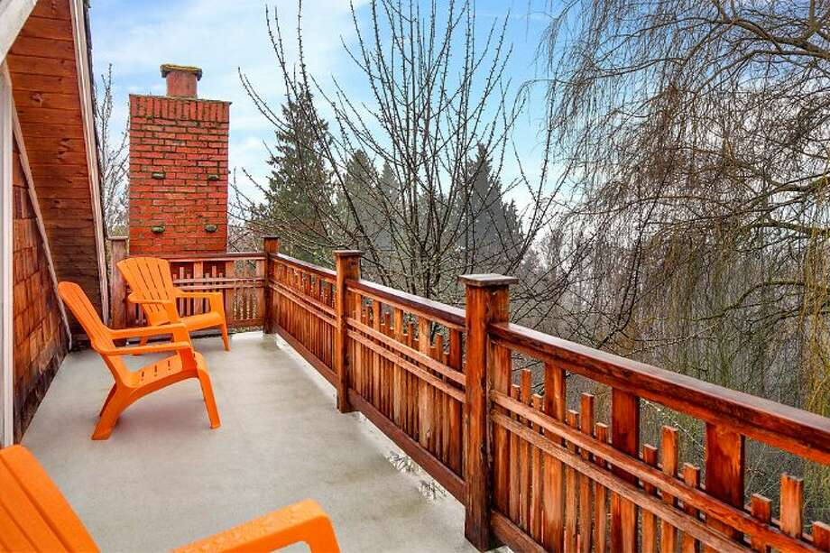 Balcony of 14036 38th Ave. N.E. The 1,590-square-foot home, built in 1999, has one bedroom, one bathroom, exposed wood beams and ceilings, a finished daylight basement, a front porch, a wrap-around deck, a patio and views of Lake Washington and the Cascades on a 10,225-square-foot lot. It's being sold with three other vacant view lots and is listed for $1.08 million. Photo: Courtesy Kelly And Kian Pornour/ Windermere Real Estate