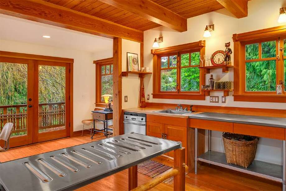 Kitchen of 14036 38th Ave. N.E. The 1,590-square-foot home, built in 1999, has one bedroom, one bathroom, exposed wood beams and ceilings, a finished daylight basement, a front porch, a wrap-around deck, a balcony, a patio and views of Lake Washington and the Cascades on a 10,225-square-foot lot. It's being sold with three other vacant view lots and is listed for $1.08 million. Photo: Courtesy Kelly And Kian Pornour/ Windermere Real Estate