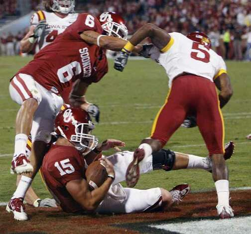 Oklahoma quarterback Drew Allen, center, falls into the end zone with a touchdown between teammate wide receiver Cameron Kenney, left, and Iowa State defensive back Jeremy Reeves, right, in the fourth quarter of an NCAA college football game in Norman, Okla., Saturday, Oct. 16, 2010. Oklahoma won 52-0. Photo: Sue Ogrocki, AP / AP