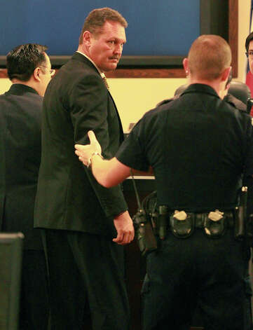 Ex-Helotes, Texas Police Chief Morton Ault (center) is led out of the 379th District Court Friday March 8, 2013 after being sentenced by Judge Ron Rangel for an alleged swindling scheme involving the repair of police vehicles. Ault was sentenced to eight years of probation and six months in jail plus financial restitution for the alleged scam. Photo: JOHN DAVENPORT, SAN ANTONIO EXPRESS-NEWS / ©San Antonio Express-News/Photo may be sold to the public