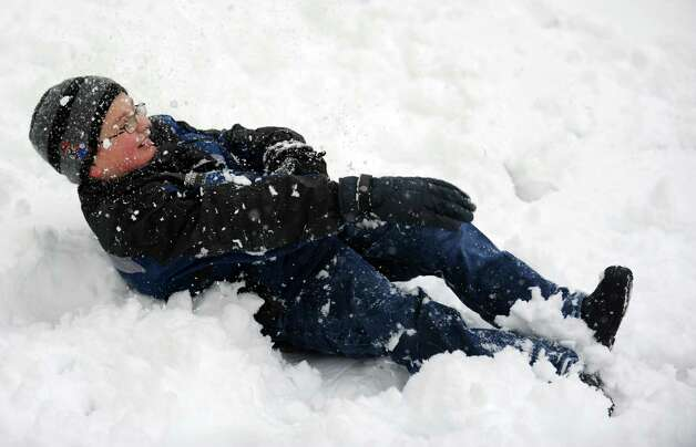 Anthony Leeney, 9, retaliates against his sister with a snowball while playing in their Ansonia backyard Friday, Mar. 8, 2013 as snow falls across the region. Photo: Autumn Driscoll