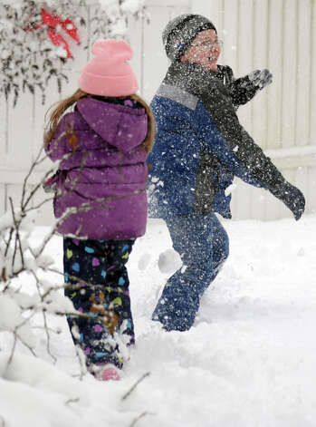 Anthony Leeney, 9, and his sister Olivia Leeney, 5, throw snowballs in their Ansonia backyard Friday, Mar. 8, 2013 as snow falls across