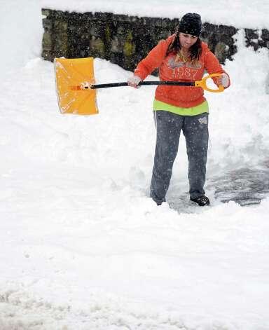 Seventeen-year-old Sammi Sardinha shovels her driveway in Ansonia, Conn. Friday, Mar. 8, 2013 as snow falls across the region. Photo: Autumn Driscoll