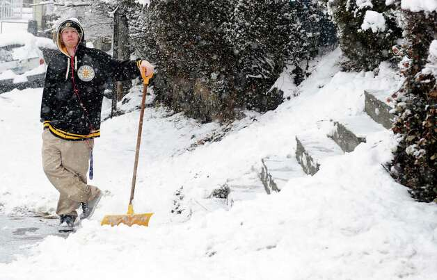 Glenn Coors pauses for a moment in his shoveling to watch a stuck vehicle on Platt Street in Ansonia, Conn. Friday, Mar. 8, 2013 as snow falls across the region. Photo: Autumn Driscoll