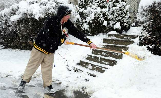 Glenn Coors shovels his steps in Ansonia, Conn. Friday, Mar. 8, 2013 as snow falls acros