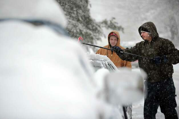 Eric Kohler clears off his car in Ansonia, Conn. Friday, Mar. 8, 2013 as snow falls across the region. Photo: Autumn Driscoll