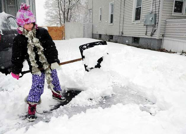 Nine-year-old Talia Lascari helps out her mom by shoveling their driveway in Ansonia, Conn. Friday, Mar. 8, 2013 as snow falls across the region. Photo: Autumn Driscoll