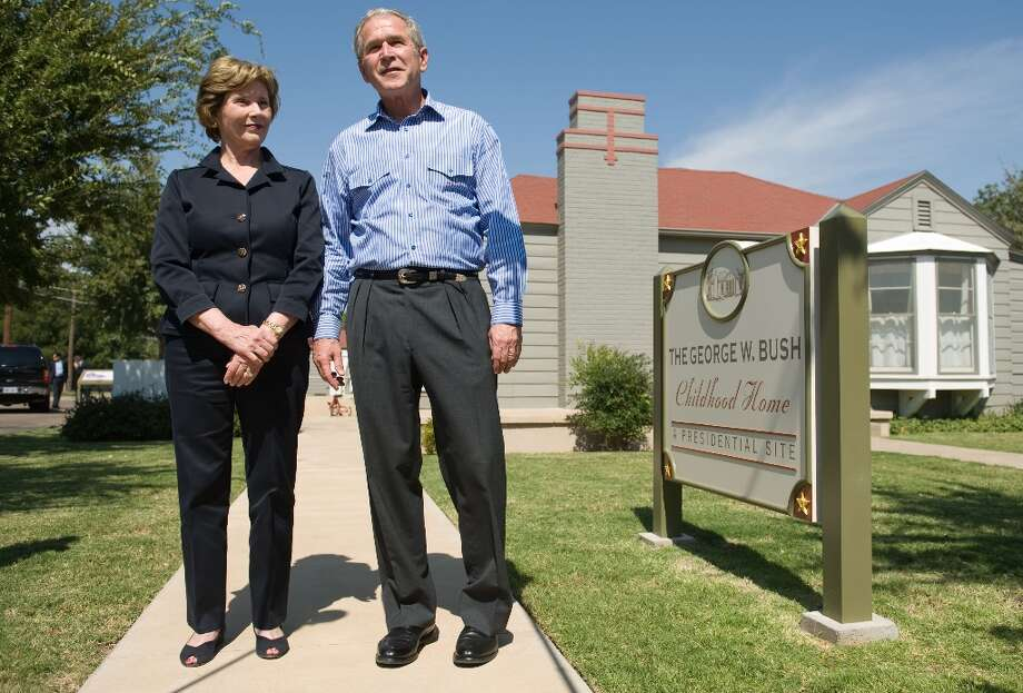 US President George W. Bush and First Lady Laura Bush speak to the media after touring the president's childhood home in Midland, Texas, on October 4, 2008. Bush traveled to attend a Republican fundraiser in the town where he grew up. AFP PHOTO / Saul LOEB Photo: SAUL LOEB, AFP/Getty Images / AFP