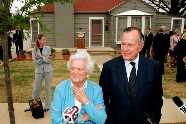 Former President George H.W. Bush, right, and Barbara Bush, left, respond to questions as they stand in front of the childhood home of George W. Bush in Midland, Texas, Tuesday, April 11, 2006. The Bushes were on hand for the official dedication of the home Tuesday.