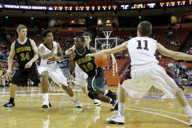 East Chambers guard Glenn Roberts (10) drives to the basket against White Oak defenders Hayden Nichols (25) and Skylar Sutton (11) during their quarter final game at the UIL State Basketball Championships in Austin at the Frank Erwin Center, Friday, March 8,  2013. East Chambers fell to White Oak 69-50.  Valentino Mauricio/For The Enterprise Photo: Valentino Mauricio