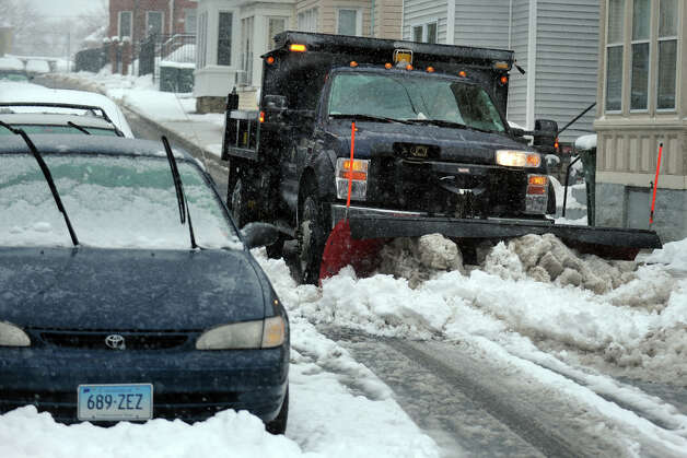 A Public Facilities truck plows snow on Armstrong Place, a narrow one way street in Bridgeport, Conn., March 18th, 2013. Photo: Ned Gerard / Connecticut Post