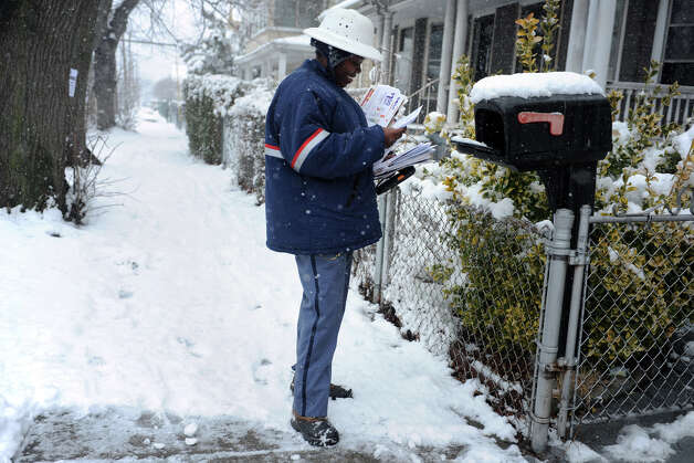 Tanya Marshall delivers mail in the snow along Noble Ave., in Bridgeport, Conn., March 18th, 2013. Photo: Ned Gerard / Connecticut Post