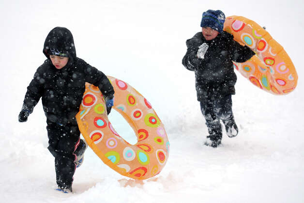 Anthony Acevedo, left, and Sean Miranda climb up a hill while sledding in Beardsley Park, in Bridgeport, Conn., March 18th, 2013. Photo: Ned Gerard / Connecticut Post